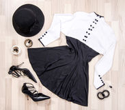 Cute dress with buttons and accessories arranged on the floor. Royalty Free Stock Images