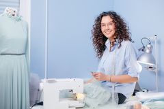 Cute dressmaker with wavy hair going to take grey bobbin of thread at workplace. Needlewoman working Stock Photos