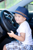Cute driver in blue hat sits in car Royalty Free Stock Images