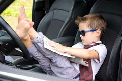 Cute driver reads newspaper in car Royalty Free Stock Photography