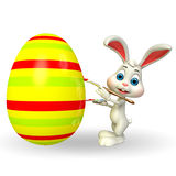 Cute Easter Bunny coloring big egg Royalty Free Stock Photo