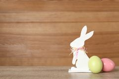 Cute Easter bunny figure and dyed eggs on table against wooden background. Space for text royalty free stock image
