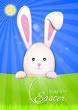 Cute Easter bunny on a sky blue background. Easter egg and greeting inscription - Happy Easter. On a green spring background. Symbol of Easter celebrations Royalty Free Stock Image