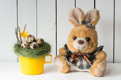 Cute Easter Bunny Stuffed Toy in a Dress Next to a Yellow Cup with Quail Eggs in a Nest on Top Royalty Free Stock Photos