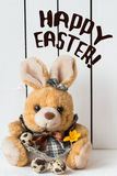 Cute Easter Bunny Stuffed Toy in a Dress with Quail Eggs and an Orange Crocus Flower Stock Images