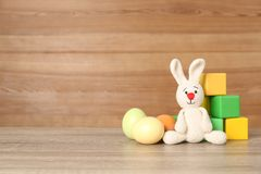 Cute Easter bunny toy near colorful cubes and dyed eggs. On table, space for text stock images
