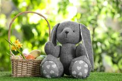 Cute Easter bunny toy and wicker basket with dyed eggs. On green grass against blurred background stock photography