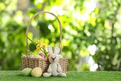 Cute Easter bunny toy with wicker basket and dyed eggs on green grass against blurred background. Space for text stock image