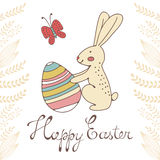 Cute easter card with easter bunny holding egg Stock Photo