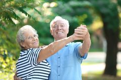 Cute elderly couple dancing outdoors. Time together stock image