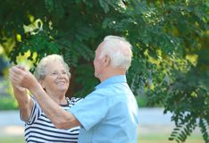 Cute elderly couple dancing outdoors royalty free stock photography