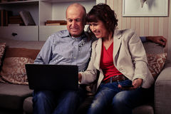 A cute elderly pair smiling and looking at a notebook Royalty Free Stock Photos