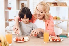 Cute elderly woman helps little boy to cut sausage on plate. Beautiful grandmother helps her grandchild to eat. royalty free stock photo