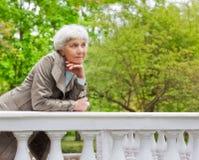 Cute elderly woman senior on the beautiful white verandah n the park Stock Photography