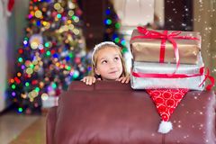 Cute elegant girl celebrate Christmas and New Year with presents. Adorable happy toddler girl wearing elegant dress sitting on leather sofa with christmas Royalty Free Stock Photos