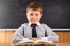 Cute boy with books at the desk Royalty Free Stock Photography