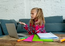 Cute elementary student feeling sad and confusing while doing difficult assignment with her laptop at home in primary school royalty free stock photos