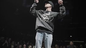 Cute active guy in dark sweater and blue jeans breakdancing on stage. Cute energetic guy dressed in dark sweater, cap and blue jeans performing breakdancing with stock video