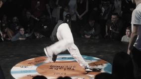 Young man in sportive dark outfit energetically breakdances at festival. Cute energetic young wearing dark stylish sportive outfit is breakdancing with stock video