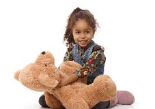 Cute ethnic girl playing with plush bear smiling stock image