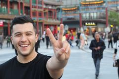 Cute ethnic guy doing the peace gesture royalty free stock image