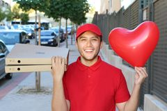 Cute ethnic pizza delivery guy holding heart shaped balloon royalty free stock images