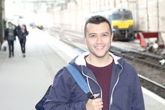 Cute ethnic young man in retro train station.  stock photography