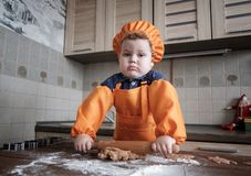 Cute European boy in a suit of the cook makes ginger cookies. Cute European boy in a chef`s cap and apron prepares ginger cookies in the kitchen at the table stock image
