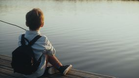 Cute European boy plays with a stick on lake pier. Little child with backpack enjoying vacation. Happy childhood. 4K. Cute European boy plays with a stick on stock footage