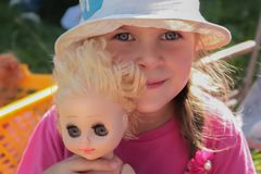 A cute European/Caucasian little girl with big blue eyes and a doll close-up in a white hat stock photos