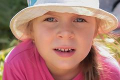 A cute European/Caucasian little girl with big blue eyes close-up in a white hat royalty free stock images