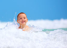 Cute excited boy having fun in waves, summer vacation Stock Images
