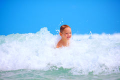 Cute excited boy having fun in waves, summer vacation Royalty Free Stock Photo