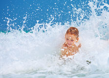 Cute excited boy having fun in waves, summer vacation Stock Photos