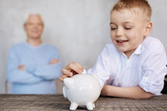 Cute excited boy putting a coin in a piggy bank. Studying basic life principles. Nice intelligent inspired kid learning new things about economy while sparing Royalty Free Stock Photos