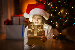 Cute excited girl looking in magic Christmas box at night Stock Images