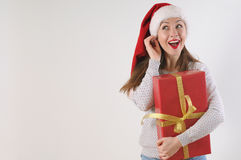 Cute exciting young woman with present box in santa hat on white Royalty Free Stock Image