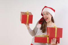 Cute exciting young woman with present boxes in santa hat on whi Stock Images