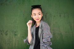 Cute exited Asian girl thinking and smiling near green wall looking to the side. royalty free stock photo