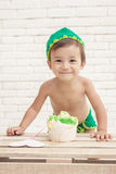 Cute expression of adorable toddler with his sponge cake Stock Photography