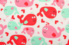 Cute fabric for kids with many beluga fish. Many pink and green fish with hearts on white as background Stock Image