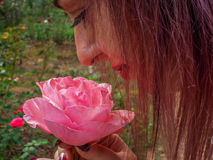 Cute face woman enjoying the smell first rose. Picture with beautiful woman enjoying the smell first rose in nature Stock Image