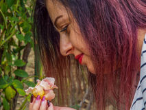 Cute face woman enjoying the smell first rose. Picture with beautiful woman enjoying the smell first rose in nature Royalty Free Stock Photography
