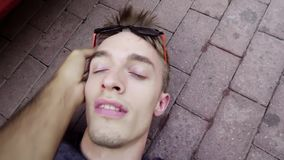 Cute fainted guy is lying on concrete ground and being awaken with slaps. Cute caucasian fainted guy wearing modern sunglasses is lying on concrete ground in stock video footage