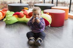 Cute fair baby girl sitting on floor in playroom sucking on toy pensively stock image