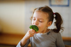 Cute fair-haired girl eats fresh broccoli. She does it with pleasure. Healthy food since the childhood royalty free stock photo