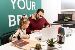 Cute fair-haired girl sitting at the desk with her bearded teacher royalty free stock photography