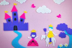 Cute fairy tale scene in felt with a princess and a prince in love in front of a fantasy castle. Cute fairy tale scene in colored felt with a princess and a stock photo