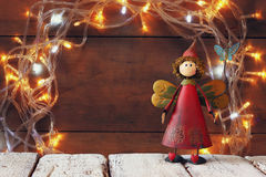Cute fairy on wooden table in front of garland gold lights background Stock Photos