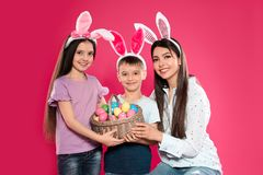 Cute family in bunny ears headbands with basket of Easter eggs on background stock photography